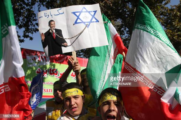 Iranian schoolboys hold national flags and a placard depicting a collar and leash tying US President Barack Obama to the Star of David with a slogan...