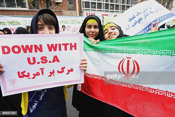 Iranian schoolgirls hold an antiUS placard next to an Iranian flag during the annual demonstration outside the former US embassy in Tehran to mark...