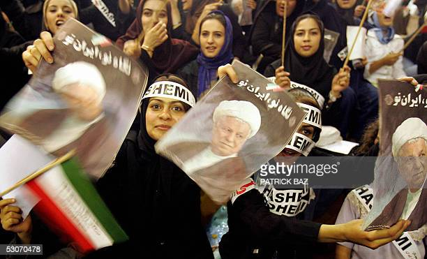 Iranian schoolgirls hold up pictures of presidential candidate Akbar Hashemi Rafsanjani during a rally exclusively for women at a female sport hall...