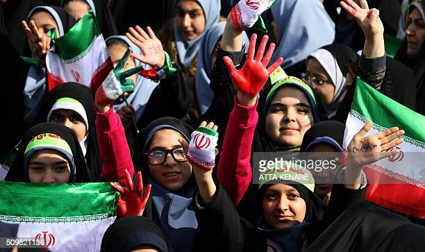 Iranian schoolgirls wave their national flag during celebrations in Tehran's Azadi Square to mark the 37th anniversary of the Islamic revolution on...