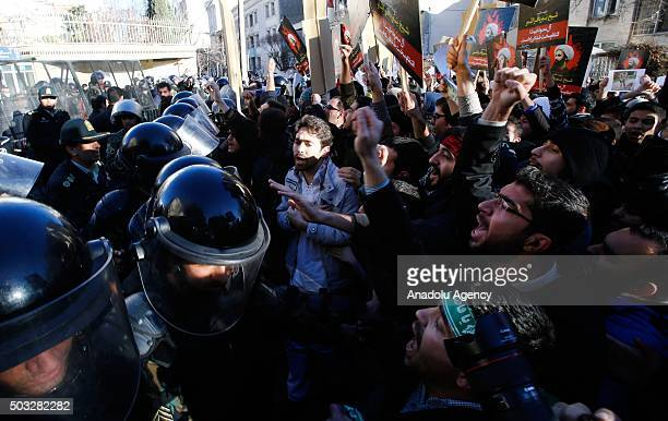 Iranian security forces members stand guard as the demonstrators hold posters of Nimr Baqir alNimr and shout slogans during a protest rally outside...