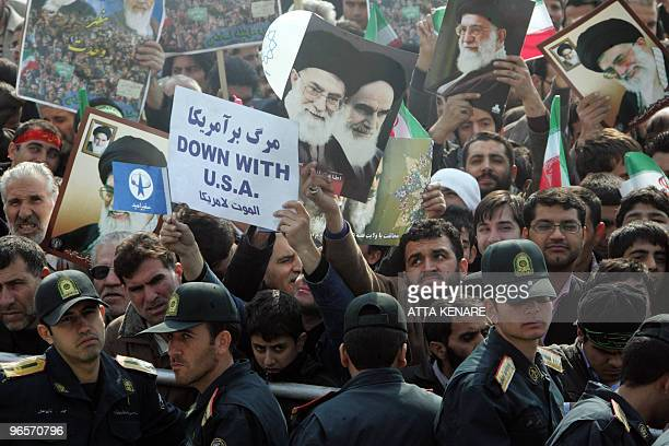 Iranian security forces stand guard as tens of thousands waving national flags antiUS placards and portraits of Supreme leader Ayatollah Ali Khamenei...