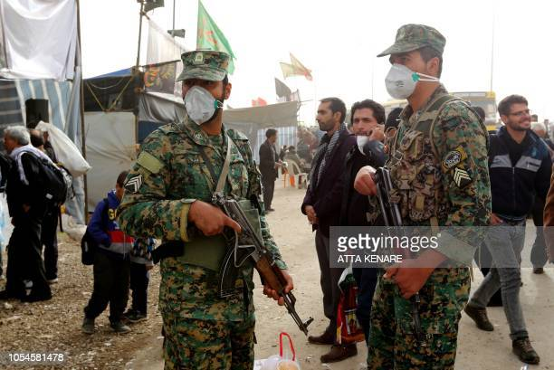 Iranian security forces stand guard at the Mehran border point between Iran and Iraq as thousands of Iranian Shiite Muslim pilgrims headed towards...