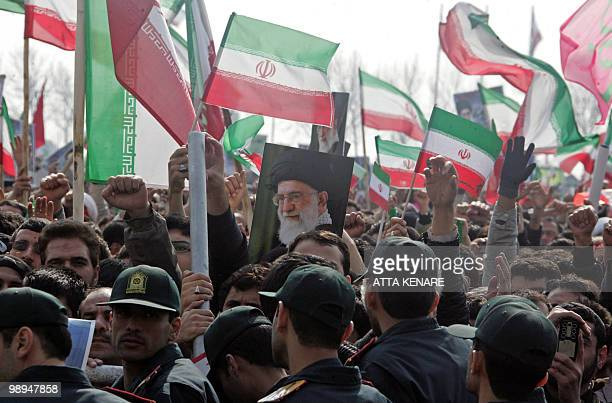 Iranian security froces stand guard as tens of thousands of Iranians waving national flags and portraits of Supreme leader Ayatollah Ali Khamenei...