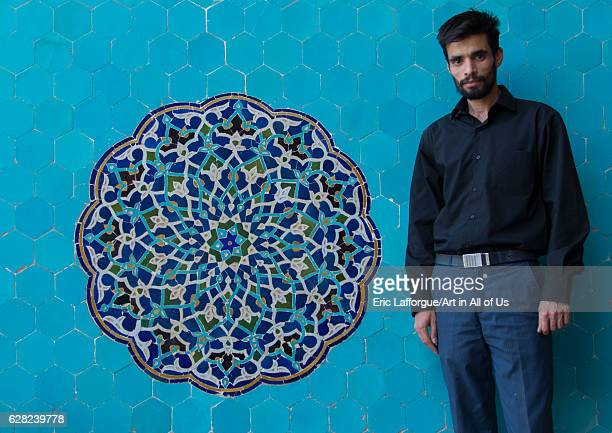 Iranian shiite man in Jameh mosque in front of a blue mosaic Yazd Province Yazd Iran on October 18 2016 in Yazd Iran