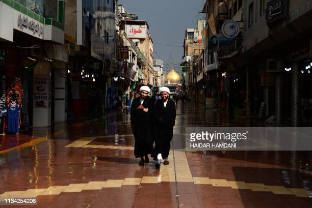 TOPSHOT Iranian Shiite Muslim clergies walk through a street in the Iraqi holy central city of Najaf on April 1 2019 as believers prepare to mark...