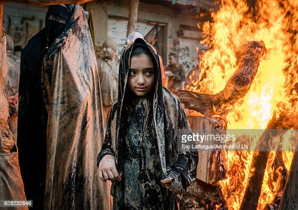 Iranian shiite muslim girls gather around a bonfire after rubbing mud on their chadors during the Kharrah Mali ritual to mark the Ashura day Lorestan...