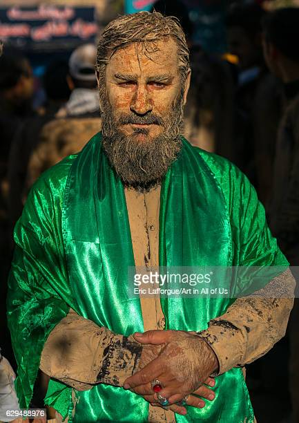 Iranian shiite muslim man with a green scarf after rubbing mud on his body during the Kharrah Mali ritual to mark the Ashura ceremony Lorestan...