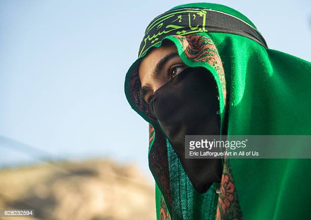 Iranian shiite muslim man with his face hidden by a veil mourning Imam Hussein on Tasua during the Chehel Manbar ceremony one day before Ashura...
