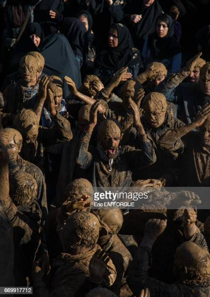 Iranian Shiite muslim men covered in mud chanting and selfflagellating during Ashura the day of the death of Imam Hussein on October 23 2015 in Bijar...