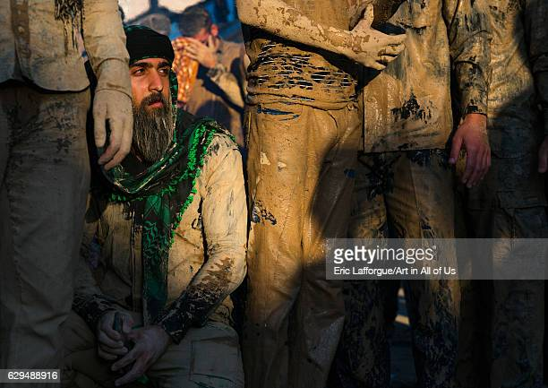 Iranian shiite muslim men gather around a bonfire after rubbing mud on their clothes during the Kharrah Mali ritual to mark the Ashura day Lorestan...