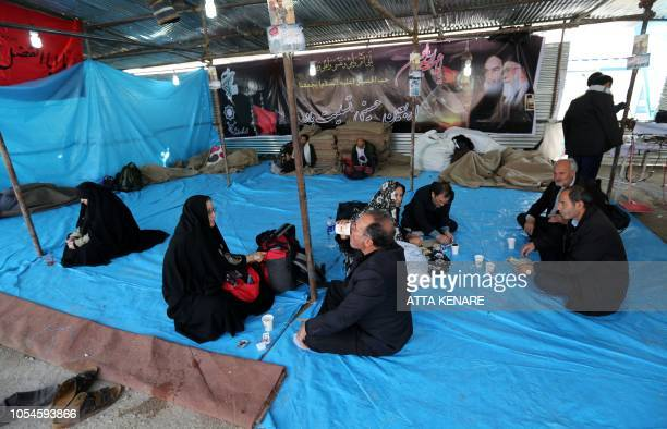 Iranian Shiite Muslim pilgrims share a meal offered by volunteers at the Mehran border point between Iran and Iraq as they head toward the central...