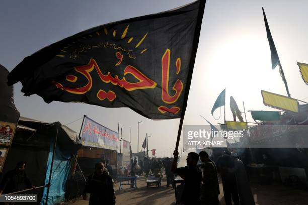 Iranian Shiite Muslim pilgrims wave flags at the Mehran border point between Iran and Iraq, as they head toward the central Iraqi shrine city of...