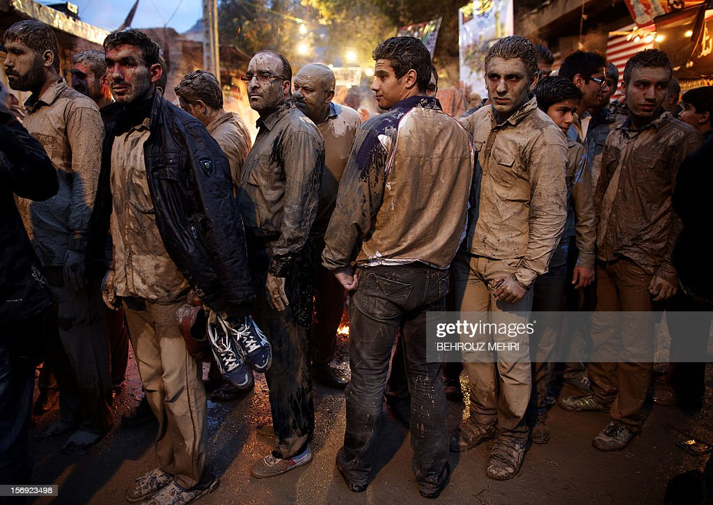 Iranian Shiite Muslims gather around a bonfire after rubbing mud on their body early in the morning, during the 'Kharrah Mali' (Mud Rubbing) ritual to mark the Ashura religious ceremony in the city of Khorramabad, some 470 kms southwest of Tehran on November 25, 2012. 'Khrreh Mali' or 'Mud Rubbing' is a ritual that is held in the city of Khorramabad every year to commemorate the seventh century slaying of Prophet Mohammed's grandson Imam Hussein, in which Iranian men roll over in mud and dry themselves by gathering around the bonfires before flagellating themselves.