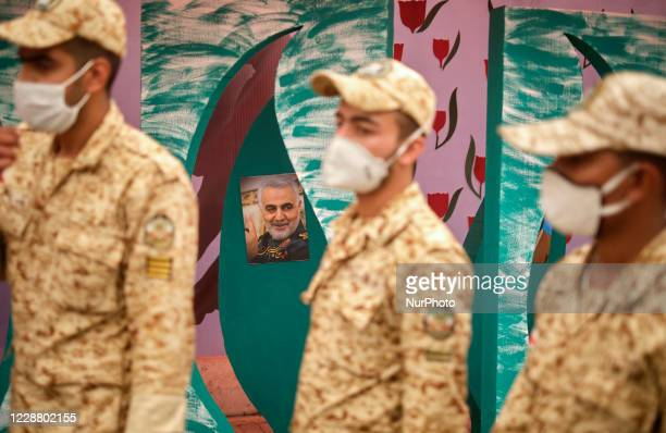 Iranian soldiers walk past a portrait of the former commander of the Islamic Revolutionary Guard Quds Force, Qasem Soleimani, during a war exhibition...