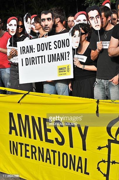 Iranian students and members of Amnesty International NGO holding a banner reading ' Where are human rights' demonstrate in front of the Iranian...