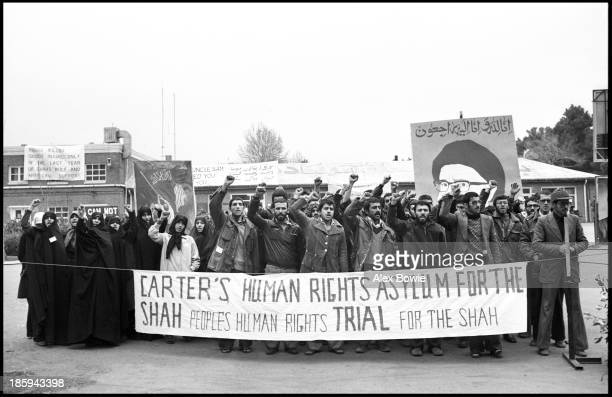 Iranian students chant Islamic slogans while standing behind a banner that reads Carter's Human Rights Asylum for the Shah – People's Human Rights...