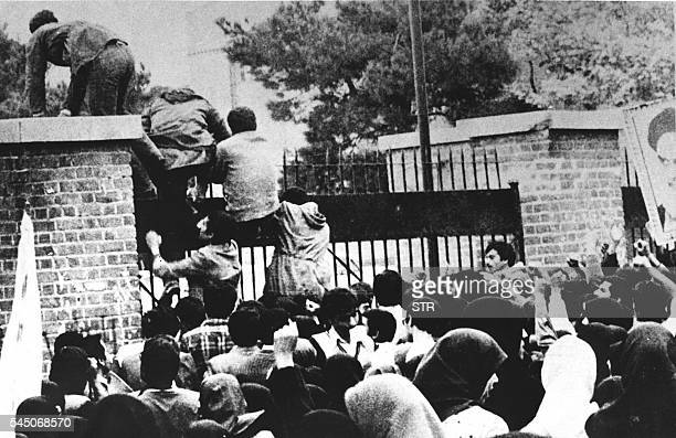 Iranian students climb over the wall of the US embassy in Tehran 04 November 1979 Twenty years later 04 November 1999 the former embassy building now...