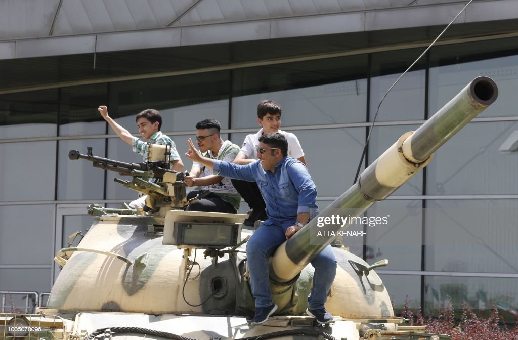 Iranian students gesture on a tank displayed at the Holy