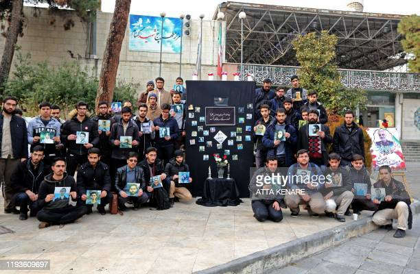 Iranian students hold pictures of victims during a memorial for the passengers of the Ukraine plane crash, in University of Tehran on January 14,...