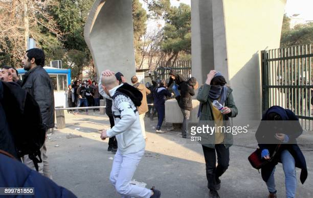 Iranian students run for cover from tear gas at the University of Tehran during a demonstration driven by anger over economic problems in the capital...