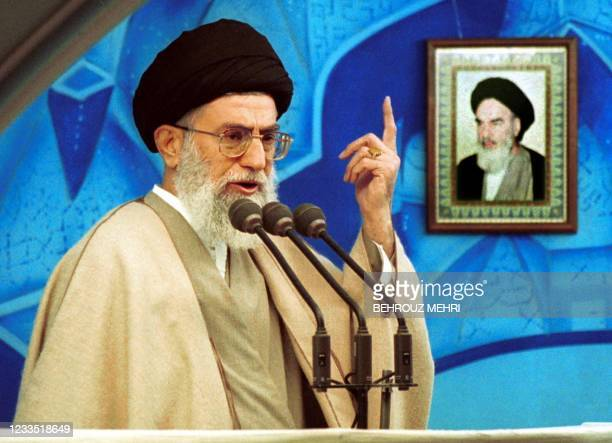 Iranian supreme leader Ayatollah Ali Khamenei delivers a sermon at Tehran University's weekly Friday prayers 15 December 2000, with a portrait of his...