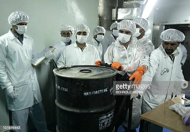 Iranian technicians remove a container of radioactive uranium 'yellow cake' sealed by the International Atomic Energy Agency to be used at the...