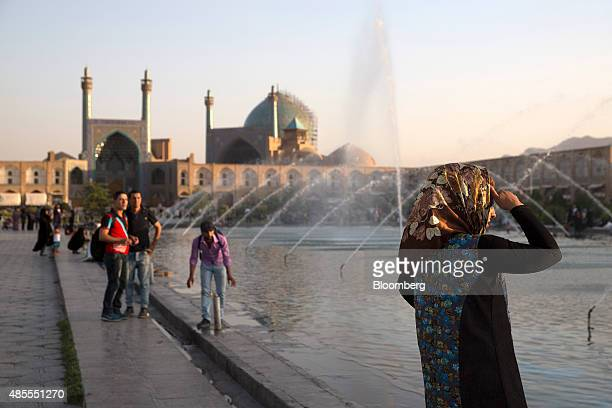 Iranian tourists watch the water fountains on Naqsh-e-Jahan square in Isfahan, Iran, on Thursday, Aug. 27, 2015. Iran expects its economic growth to...