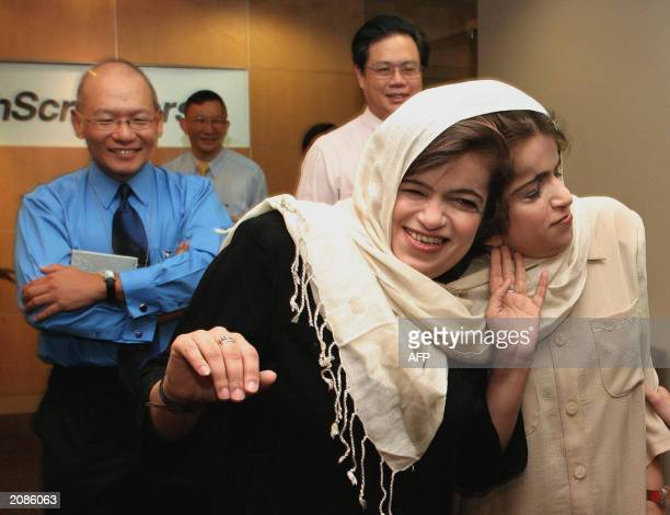 Iranian twins Ladan and Laleh Bijani give a press conference at Raffles Hospital in Singapore 11 June 2003 as coleader of the surgery team...
