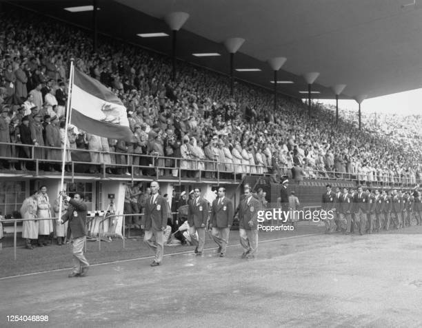Iranian weightlifter Mahmoud Namjoo is the flag bearer leading the Iranian Olympic team at the opening ceremony of the 1952 Summer Olympics at the...