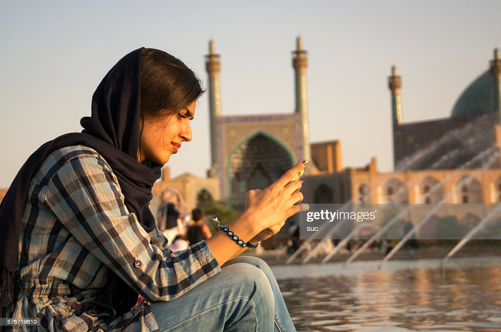 Iranian woman checking her mobile phone : Stock Photo