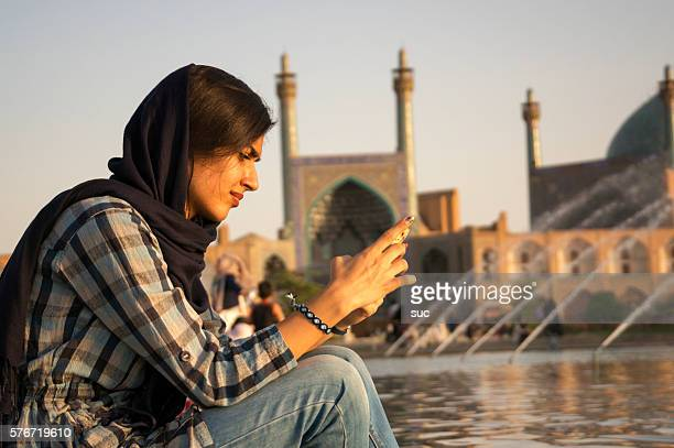 iranian woman checking her mobile phone - iranian woman stock photos and pictures