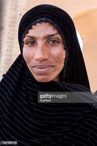 Iranian woman from Balochistan region of so called Baloch people in black chador sits on a street of Yazd on September 17 2018