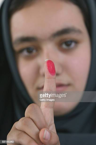 Iranian woman shows their inkstained finger after casting her ballot in the second round of the Iranian presidential election on June 24 2005 in...
