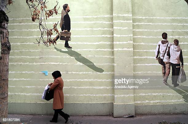 Iranian woman walks past a wall painting in Tehran Iran on the first anniversary of nuclear deal between Iran and world powers on January 16 2017...
