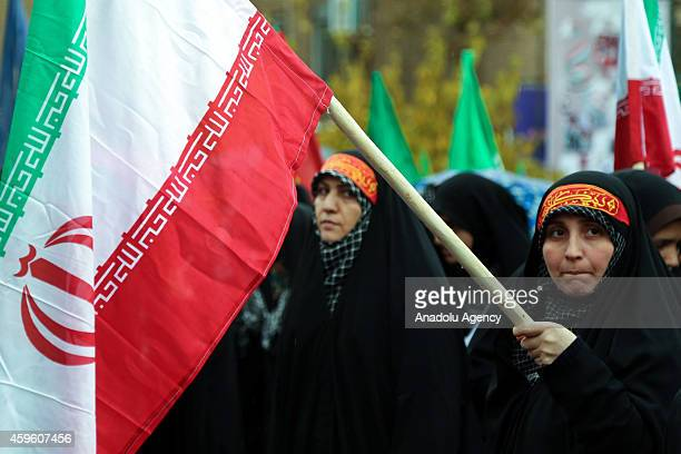 Iranian woman waves Iranian flag during the celebrations marking the 35th anniversary of the Basij , a paramilitary volunteer militia established in...