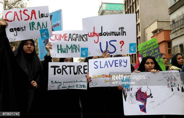 Iranian women carrying placards during a demonstration outside the former US embassy in the Iranian capital Tehran on November 4 marking the...