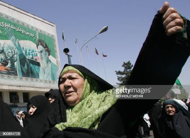 Iranian women chant slogans under a portrait of Iran's late founder of the Islamic Republic Ayatollah Khomeini during a demonstration to protest...