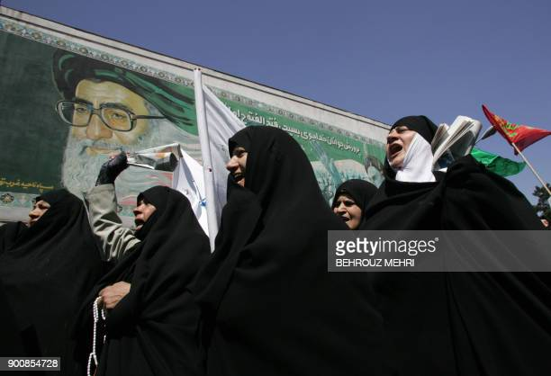 Iranian women chant slogans under a portrait of Iran's supreme leader Ali Khamenei during a demonstration to protest against women who violate the...