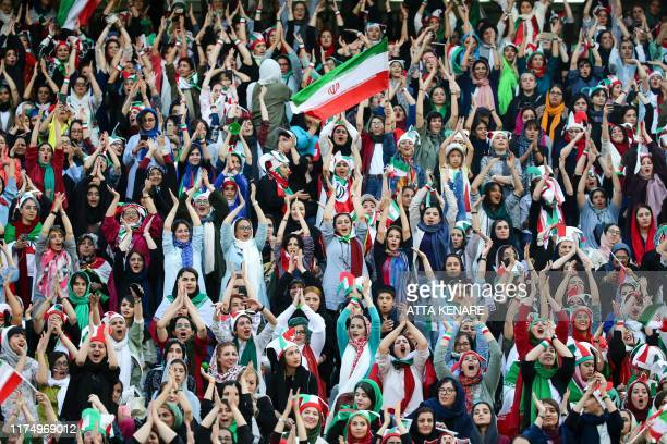 Iranian women cheer during the World Cup Qatar 2022 Group C qualification football match between Iran and Cambodia at the Azadi stadium in the...