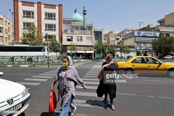 Iranian women cross a street in downtown Tehran on July 20 as authorities tighten restrictions amid the COVID-19 pandemic. - Iran a day earlier...