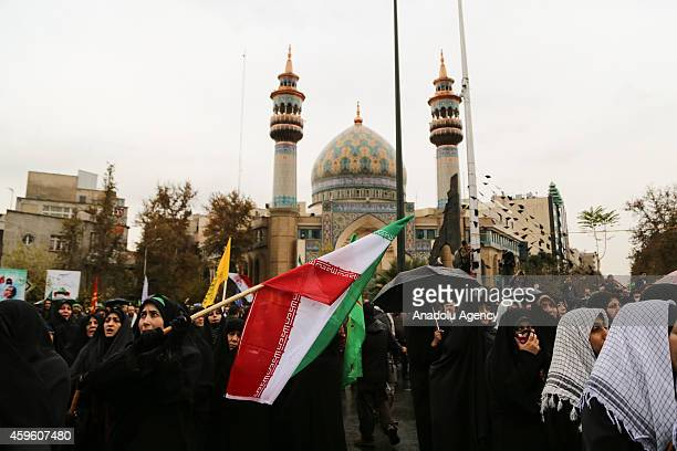 Iranian women hold flags during the celebrations marking the 35th anniversary of the Basij , a paramilitary volunteer militia established in 1979 by...