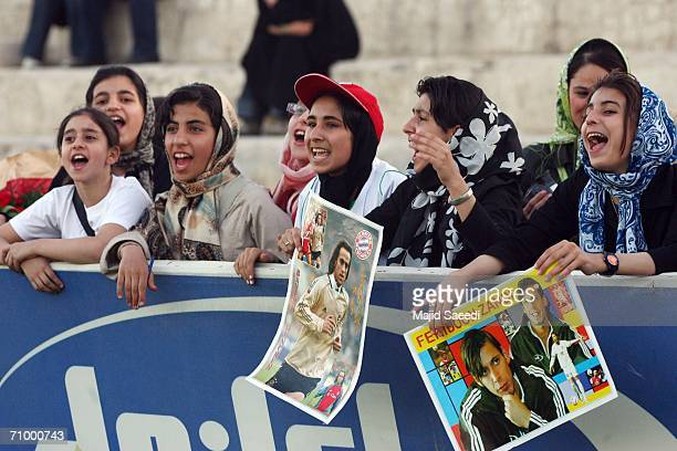 Iranian women hold portraits of Iran's national football players Ali Karimi and Ferydoon Zandi while watching Iran's national football team exercise...