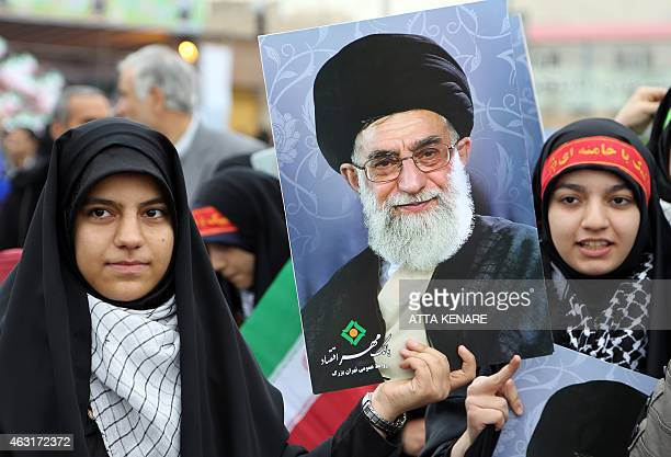 Iranian women hold posters of Iran's Supreme Leader Ayatollah Ali Khamenei durring a rally in Tehran's Azadi Square to mark the 36th anniversary of...