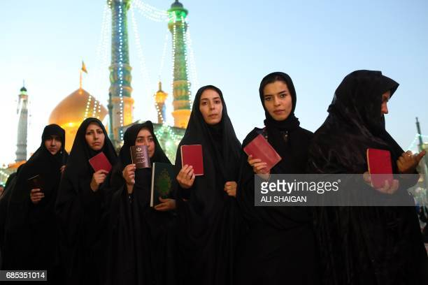 TOPSHOT Iranian women hold their ID as they wait in line to cast their votes for municipal and presidential elections at a polling station at the...