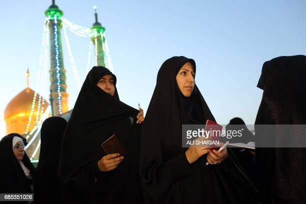 Iranian women hold their ID as they wait in line to cast their votes for municipal and presidential elections at a polling station at the Massoumeh...