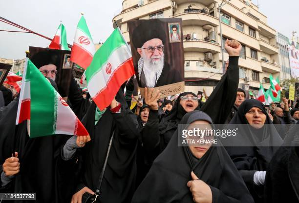Iranian women holding national flags and pictures of the Islamic republic's supreme leader, Ayatollah Ali Khamenei, take part a pro-government...