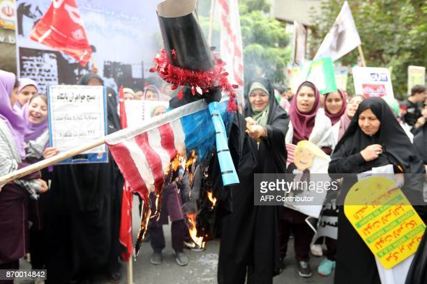 Iranian women light a US flag on fire outside the former US embassy in the Iranian capital Tehran on November 4 during a demonstration marking the...