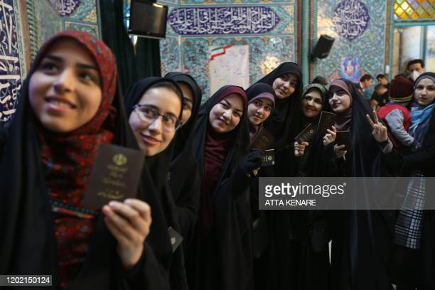 Iranian women line up before casting their votes in a parliamentary election at a polling station in Tehran on February 21 2020 Iranians began voting...