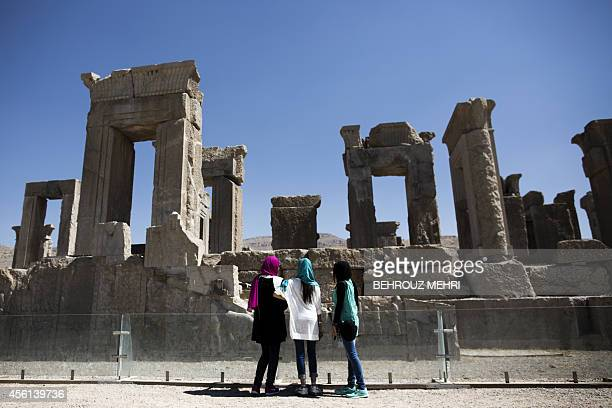 Iranian women look at the palace of King Darius of Achaemenid in the ancient Persian city of Persepolis near Shiraz in southern Iran on September 26,...
